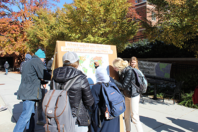 Students pin the places they would like to travel as part of Geography Awareness Week activities on the Burchfiel plaza.